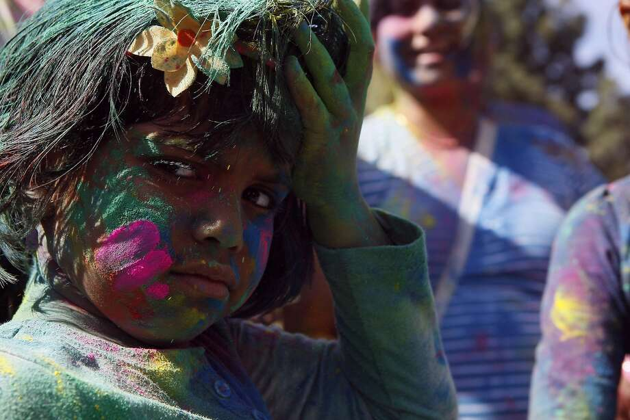 Aarya Shetty, 5, takes a break from the festivities during a Holi celebration at the Vedic Dharma Samaj Fremont Hindu Temple on March 16, 2014 in Fremont, Calif. The Hindu celebration which features people throwing brightly colored powders at one another has become increasingly popular among different groups. Photo: Codi Mills, The Chronicle