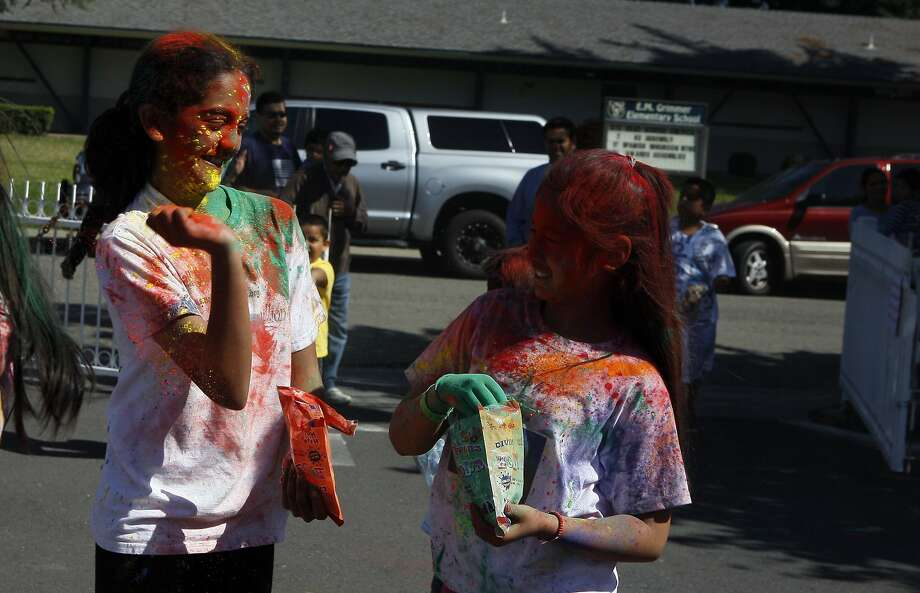 Kayal Rajkumar, 13, (left) prepares to throw a handful of color at another child's face during a Holi celebration at the Vedic Dharma Samaj Fremont Hindu Temple on March 16, 2014 in Fremont, Calif. The Hindu celebration which features people throwing brightly colored powders at one another has become increasingly popular among different groups. Photo: Codi Mills, The Chronicle