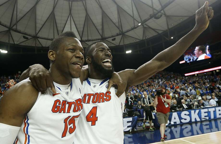 Florida's Will Yeguete and Patric Young celebrate an SEC tournament title in Atlanta after the Gators barely held off Kentucky. The Gators are the No. 1 overall seed in the NCAA tourney. Photo: John Bazemore, Associated Press