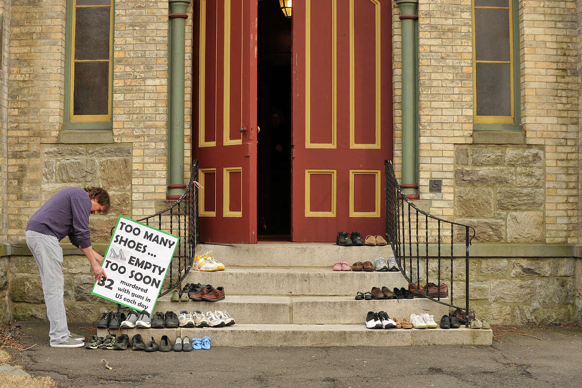 Norris Wakefield affixes a sign next to shoes on the steps of the Unitarian Universalist Society in Stamford, Conn., before the start of the Interfaith Council of Southwestern Connecticut's vigil to prevent gun violence as part of the nation-wide Gun Violence Prevention Sabbath weekend on Sunday, March 16, 2014. People were asked to leave a pair of shoes on the church steps in remembrance of the people that no longer occupy the shoes because of gun violence.