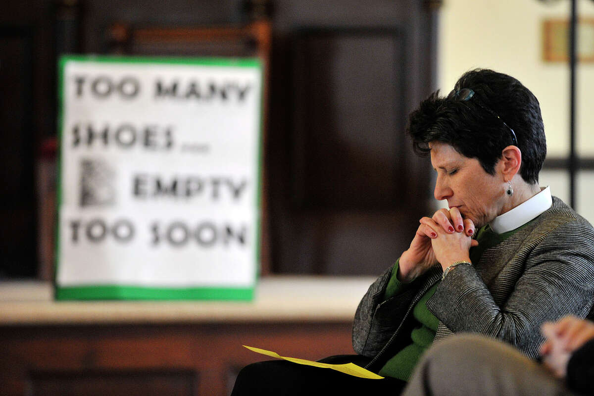 Rev. Kate Heichler, executive director of the Interfaith Council, sits in prayer as the invocation is given during the Interfaith Council of Southwestern Connecticut's vigil to prevent gun violence as part of the nation-wide Gun Violence Prevention Sabbath weekend at the Unitarian Universalist Society in Stamford, Conn., on Sunday, March 16, 2014.