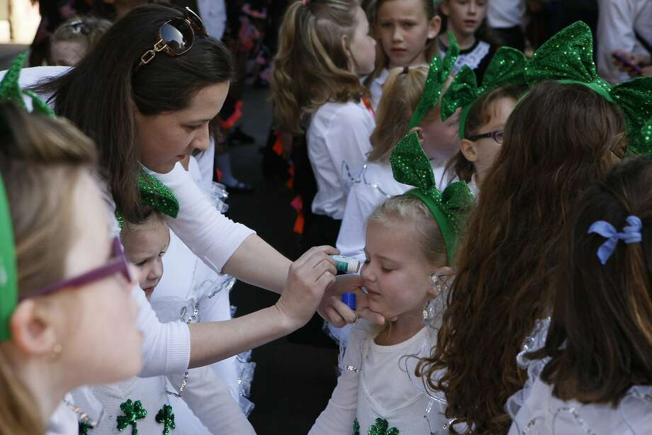 Teresa Cassidy, 30, (left) puts sunscreen on Lucy Cassidy, 4, (right) before the St. Patrick's Day Parade on March 15, 2014 in San Francisco, Calif. The 163rd annual parade ran from down a packed 2nd Street and Market to the Civic Center with dozens of floats. Photo: Codi Mills, The Chronicle