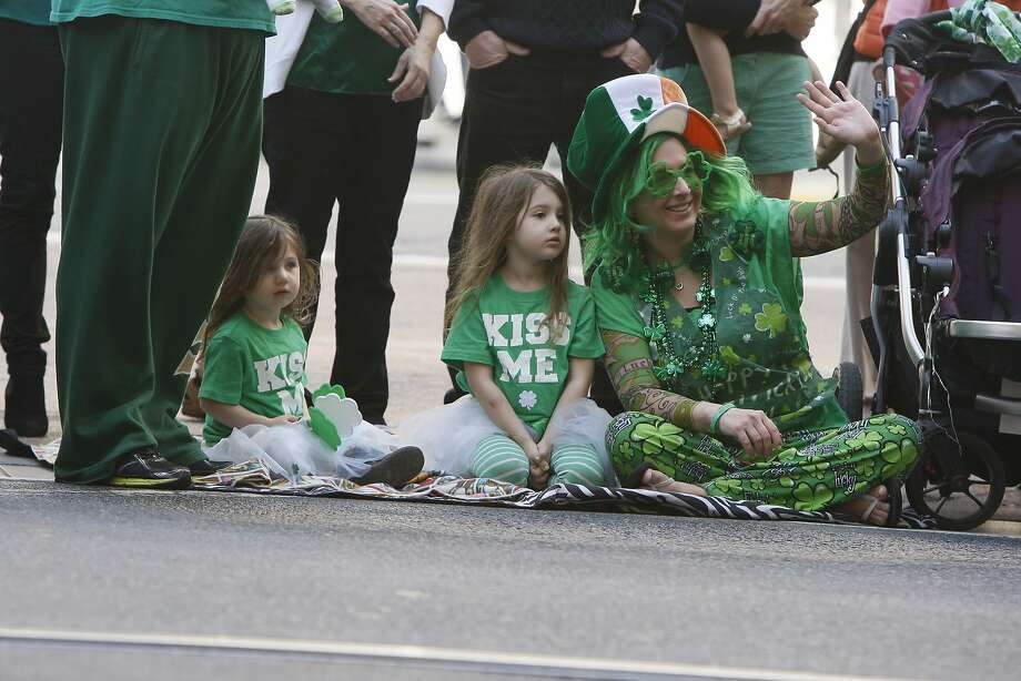 Riley O'Rourke, 2, (left) Guinevere O'Rourke, 4, (center) and Jenni O'Rourke (right) sit on the ground during the St. Patrick's Day Parade on March 15, 2014 in San Francisco, Calif. The 163rd annual parade ran from down a packed 2nd Street and Market to the Civic Center with dozens of floats. Photo: Codi Mills, The Chronicle