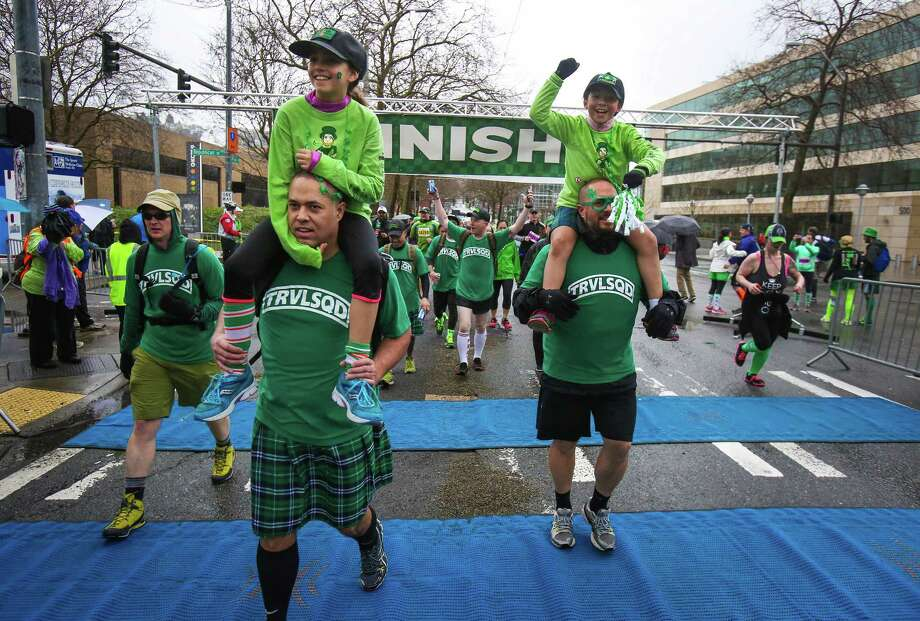 Adrianna Hyke, 10, rides on the shoulders of her dad Frank Hyke, left, as Mia Hyke, 8, rides on the shoulders of her dad, Fergus Hyke, as they cross the finish line during the annual St. Patrick's Day Dash. Thousands of runners participated in the run on Sunday, March 16, 2014. The event benefits the Detlef Schrempf Foundation. Photo: JOSHUA TRUJILLO, SEATTLEPI.COM / SEATTLEPI.COM