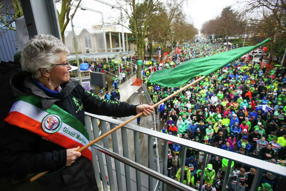 Irish Senator Katherine Zappone waves a flag to start the race during the annual St. Patrick's Day Dash. Thousands of runners participated in the run on Sunday, March 16, 2014. The event benefits the Detlef Schrempf Foundation.