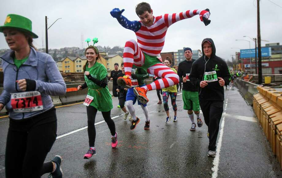 A runner takes a leap while running the course during the annual St. Patrick's Day Dash. Thousands of runners participated in the run on Sunday, March 16, 2014. The event benefits the Detlef Schrempf Foundation. Photo: JOSHUA TRUJILLO, SEATTLEPI.COM / SEATTLEPI.COM
