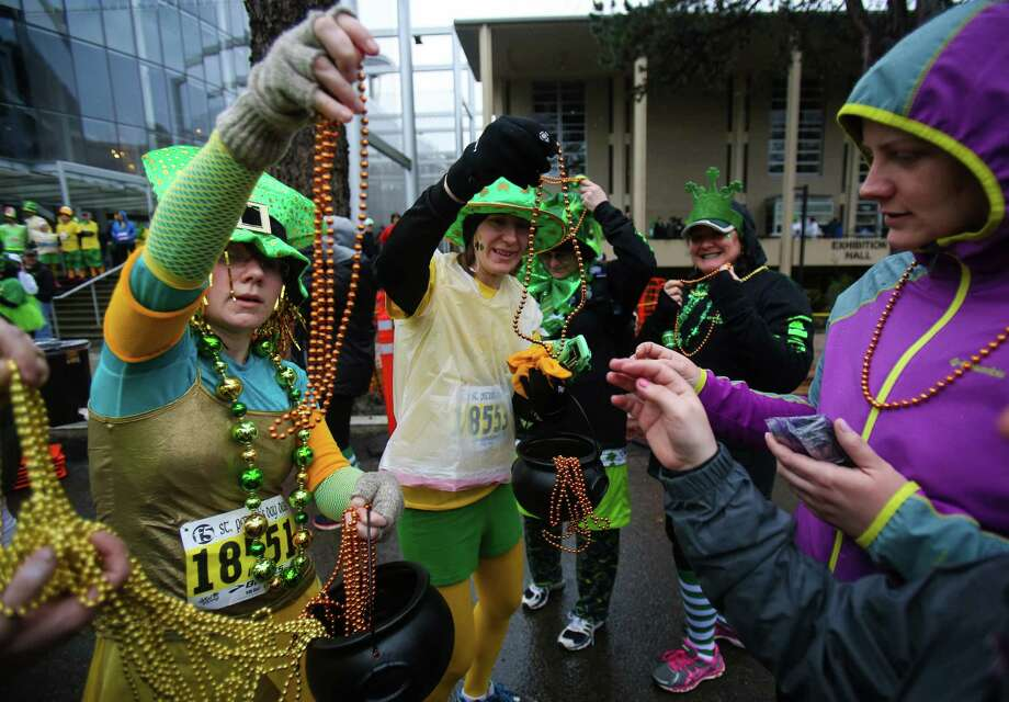Runners pass out beads during the annual St. Patrick's Day Dash. Thousands of runners participated in the run on Sunday, March 16, 2014. The event benefits the Detlef Schrempf Foundation. Photo: JOSHUA TRUJILLO, SEATTLEPI.COM / SEATTLEPI.COM