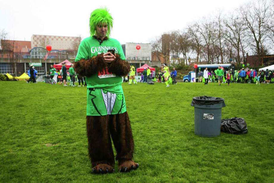 Mark Wieland sends a text message during the annual St. Patrick's Day Dash. Thousands of runners participated in the run on Sunday, March 16, 2014. The event benefits the Detlef Schrempf Foundation. Photo: JOSHUA TRUJILLO, SEATTLEPI.COM / SEATTLEPI.COM