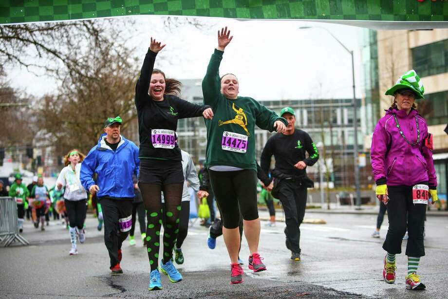 Competitors cross the finish line in style during the annual St. Patrick's Day Dash. Thousands of runners participated in the run on Sunday, March 16, 2014. The event benefits the Detlef Schrempf Foundation. Photo: JOSHUA TRUJILLO, SEATTLEPI.COM / SEATTLEPI.COM