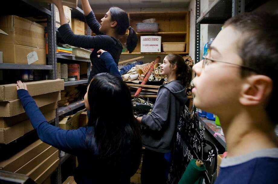 Kim Lang, 12, Priya Gada, 13, and Claire Howlett, 13, clear shelves in a storage closet as Luke Dawson, 12, stands by as students at Cloonan Middle School clean up an old art room to make way for a student lounge for a new peer mentoring group at the school.   Eighth graders in the group will help sixth graders adjust to middle school and adolescence in Stamford , Conn. on Tuesday, Feb. 9  2010. Photo: Kathleen O'Rourke / Stamford Advocate