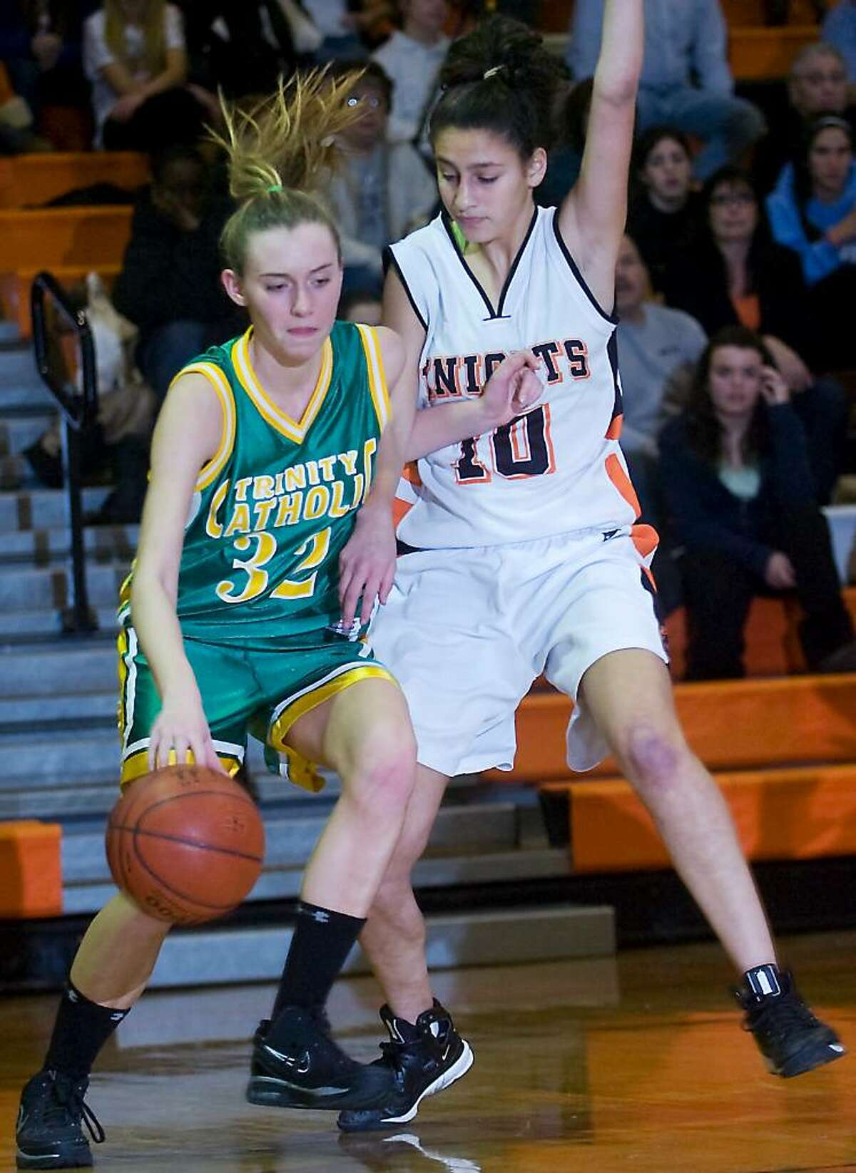 Trinity Catholic's Cayleigh Griffin controls the ball with pressure from Stamford High's Lauren Schapiro in the girls basketball city title game in Stamford, Conn. on Tuesday, Feb. 9, 2010.
