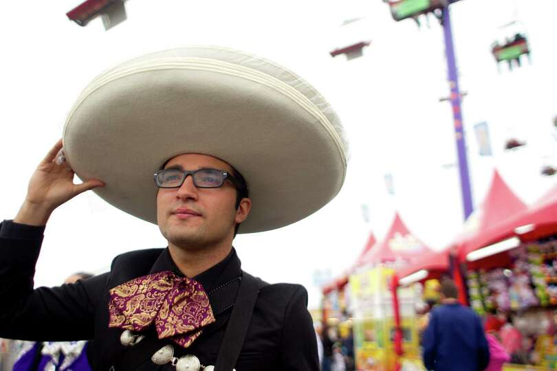 Mariachi performer, Joey Nunez, walks through the Houston Livestock Show and Rodeo midway on Go Teja