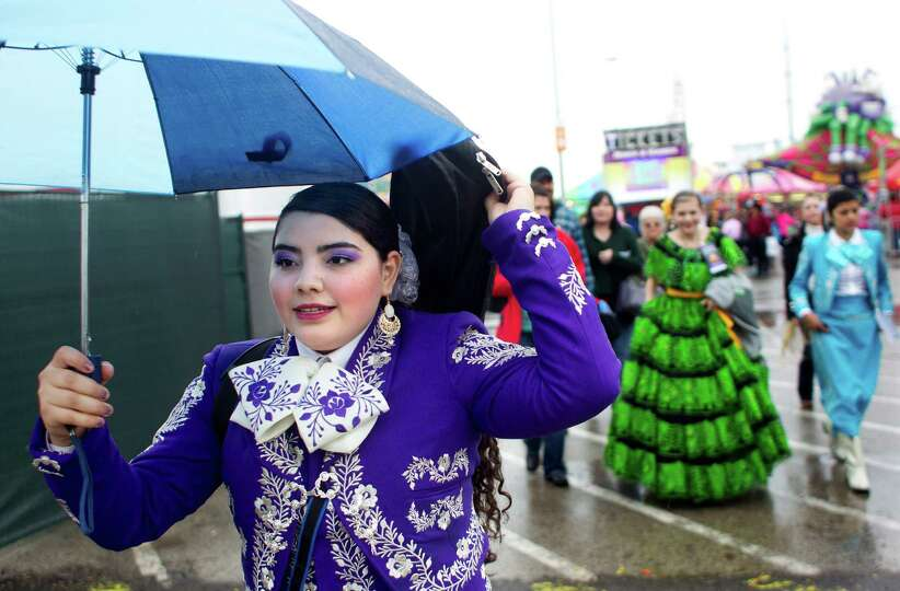 Mariachi performer, Angela Salas, walks through the rain Houston Livestock Show and Rodeo midway on