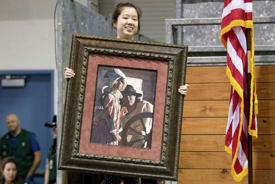 "Seo Woo ""Michelle"" Jong, 18, a senior at Memorial High School holds her painting title ""Reminiscence of Youth,"" during the Houston Livestock Show and Rodeo School Art Auction where her painting tied the show record selling for $210,000 Sunday, March 16, 2014, in Houston. Photo: Johnny Hanson, Houston Chronicle / © 2014  Houston Chronicle"