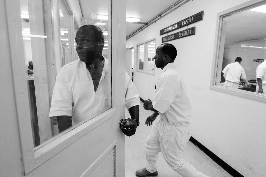 (l-r) Inmates Lawrence Burks Jr and Danny Lacy transition between classes Thursday March 6, 2014 at the Darrington Unit prison in Rosharon, TX.  A select group of inmates serving long term sentences are taking courses through Southwestern Baptist Theological Seminary. SBTS  started an accredited B.S. program in Biblical Studies at the Darrington Unit in the fall of 2011. Norwood originated the idea for the seminary at the Darrington  penitentiary. Photo: Billy Smith II, Chronicle / © 2014 Houston Chronicle