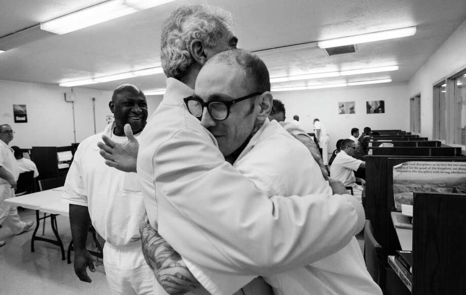 Grove Norwood, chairman of the Heart of Texas Foundation, hugs inmate Warren Bishop,Thursday March 6, 2014 at the Darrington Unit prison in Rosharon, TX.  A select group of inmates serving long term sentence are taking courses through Southwestern Baptist Theological Seminary. SBTS  started an accredited B.S. program in Biblical Studies at the Darrington Unit in the fall of 2011. Norwood originated the idea for the seminary at the Darrington  penitentiary. Photo: Billy Smith II, Chronicle / © 2014 Houston Chronicle
