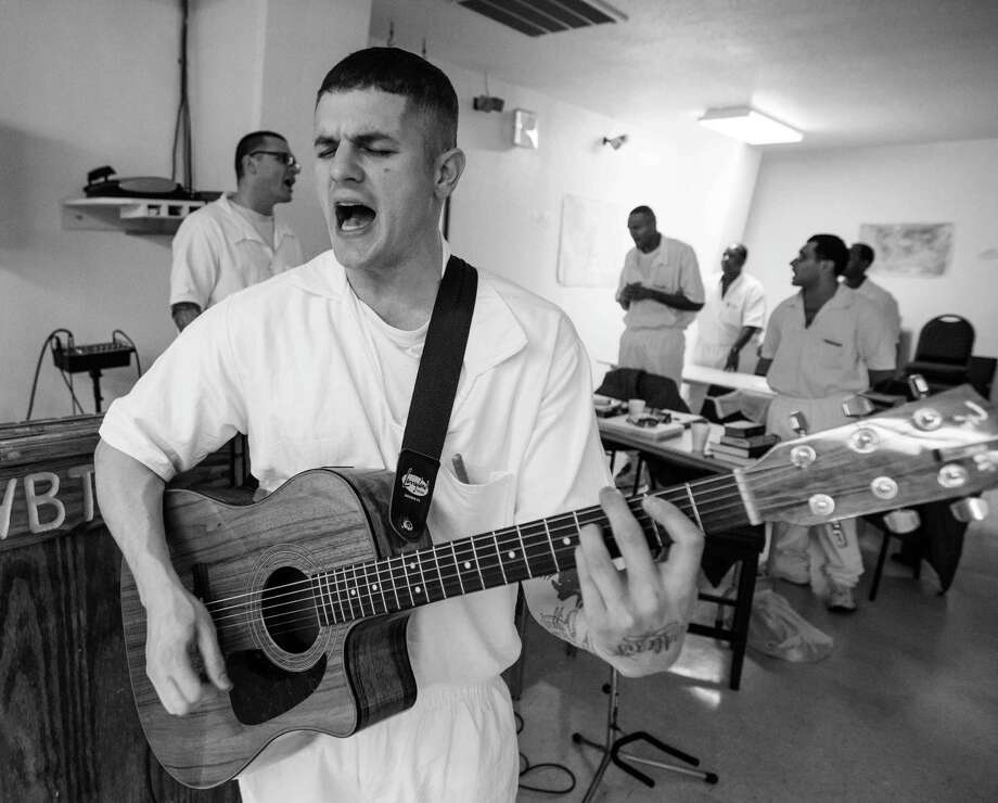 Student inmate John Montana kicks off seminary class with a song Thursday March 6, 2014 at the Darrington penitentiary in Rosharon, TX.  A select group of inmates serving long term sentences are taking courses through Southwestern Baptist Theological Seminary. SBTS  started an accredited B.S. program in Biblical Studies at the Darrington Unit in the fall of 2011. Photo: Billy Smith II, Chronicle / © 2014 Houston Chronicle