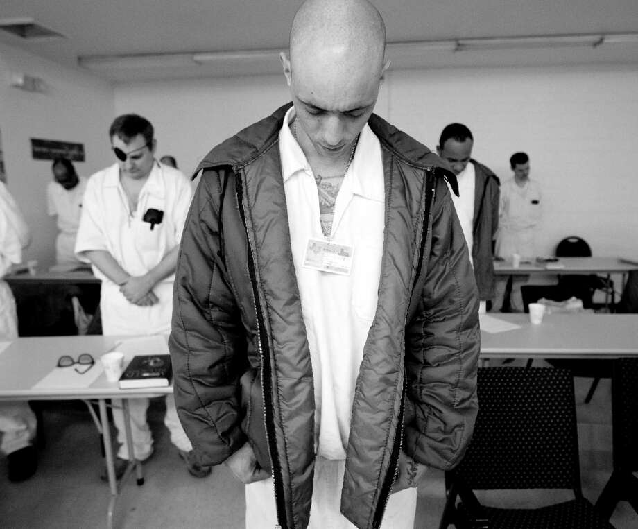 Student inmate Scott Copeland bows his head in prayer before the start of his class Thursday March 6, 2014 at the Darrington Unit prison in Rosharon, TX.  A select group of inmates serving long term sentences are taking courses through Southwestern Baptist Theological Seminary. SBTS  started  an accredited B.S. program in Biblical Studies at the Darrington Unit in the fall of 2011. Photo: Billy Smith II, Chronicle / © 2014 Houston Chronicle