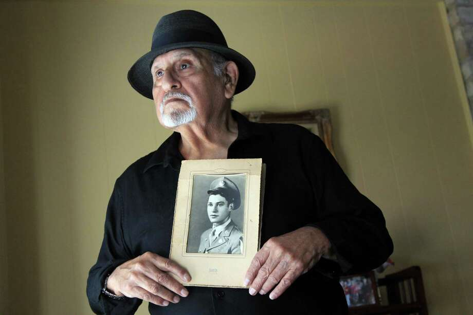 Kenny Pena holds a photograph of his brother, Army Master Sgt. Michael C. Pena, who will be recognized Tuesday as a Medal of Honor recipient for heroism during the Korean War in 1950. Photo: Mayra Beltran, Staff / © 2014 Houston Chronicle