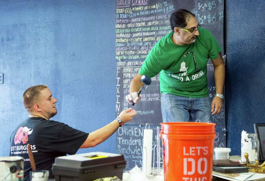 Volunteers, like Just Burgers cook Chris Graves, left, and foodie Nick Rama, are painting, cleaning and repairing the floors at the 30-year-old building from which Just Burgers in Spring operates. Photo: Craig Hartley, Freelance / Copyright: Craig H. Hartley