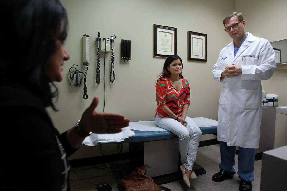 Patricia Hildenbrand, center, a 21-year-old from Baytown, was diagnosed with moyamoya, a rare cerebrovascular disease. Her mom, Sandra Salinas, talks with  Dr. Gavin Britz, one of the top moyamoya experts, following her daughter's surgery. Photo: Mayra Beltran, Staff / © 2014 Houston Chronicle