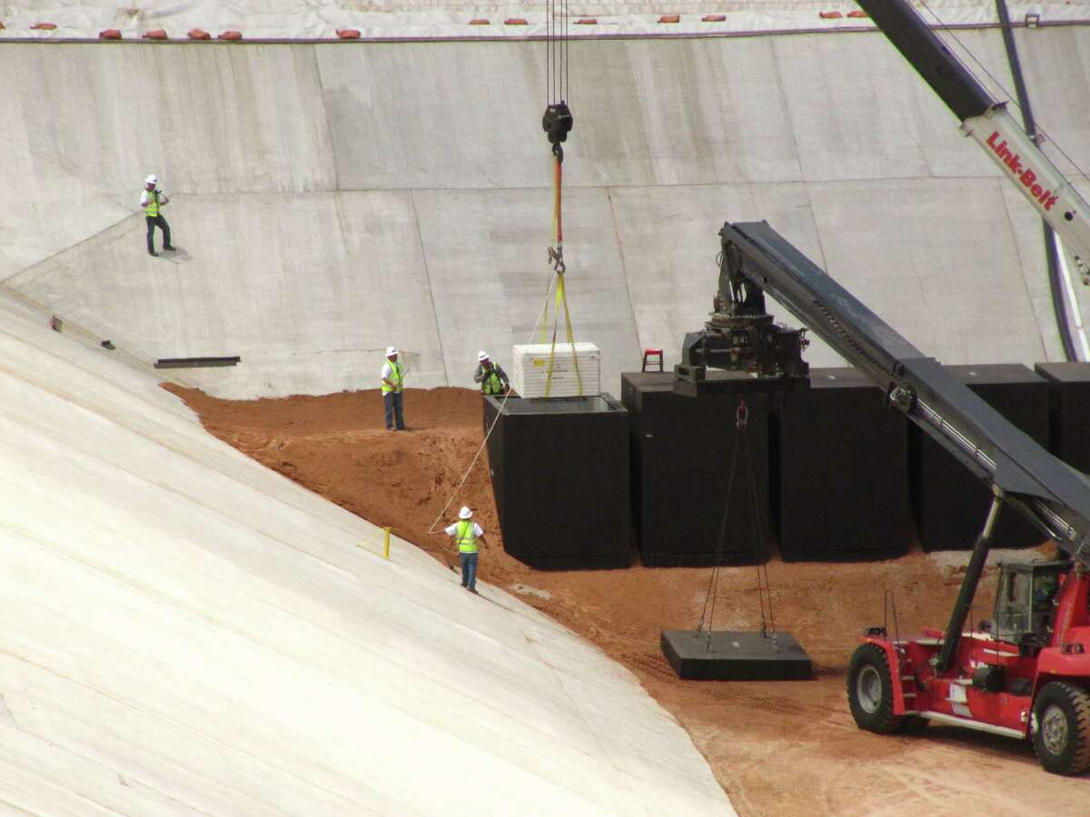 In 2013, crews from Waste Control Specialists load the first of two containers with low-level radioactive waste from Los Alamos National Laboratory in New Mexico, into a reinforced 8-inch-thick concrete container at the 90-acre federal dump where it will remain forever, near Andrews, Texas.