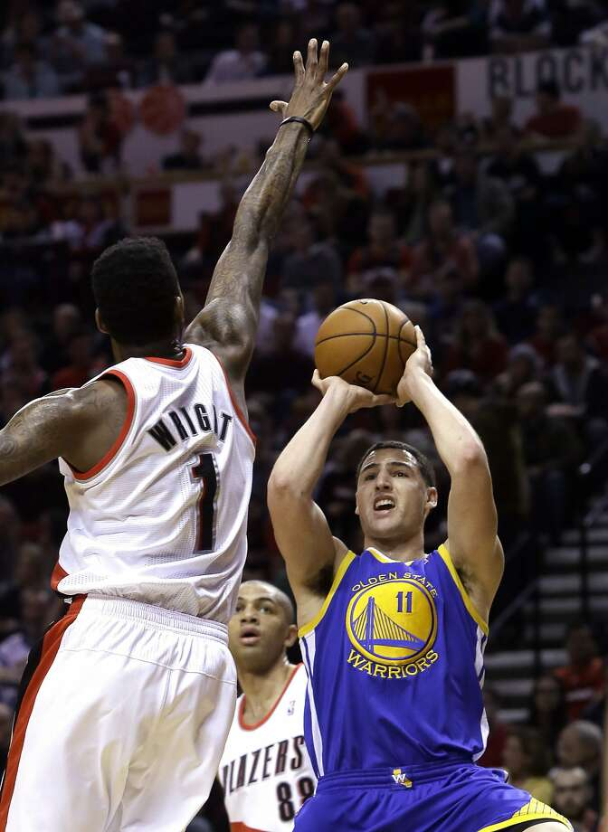 Golden State Warriors guard Klay Thompson, right, shoots against Portland Trail Blazers forward Dorell Wright during the first half of an NBA basketball game in Portland, Ore., Sunday, March 16, 2014. (AP Photo/Don Ryan) Photo: Don Ryan, Associated Press
