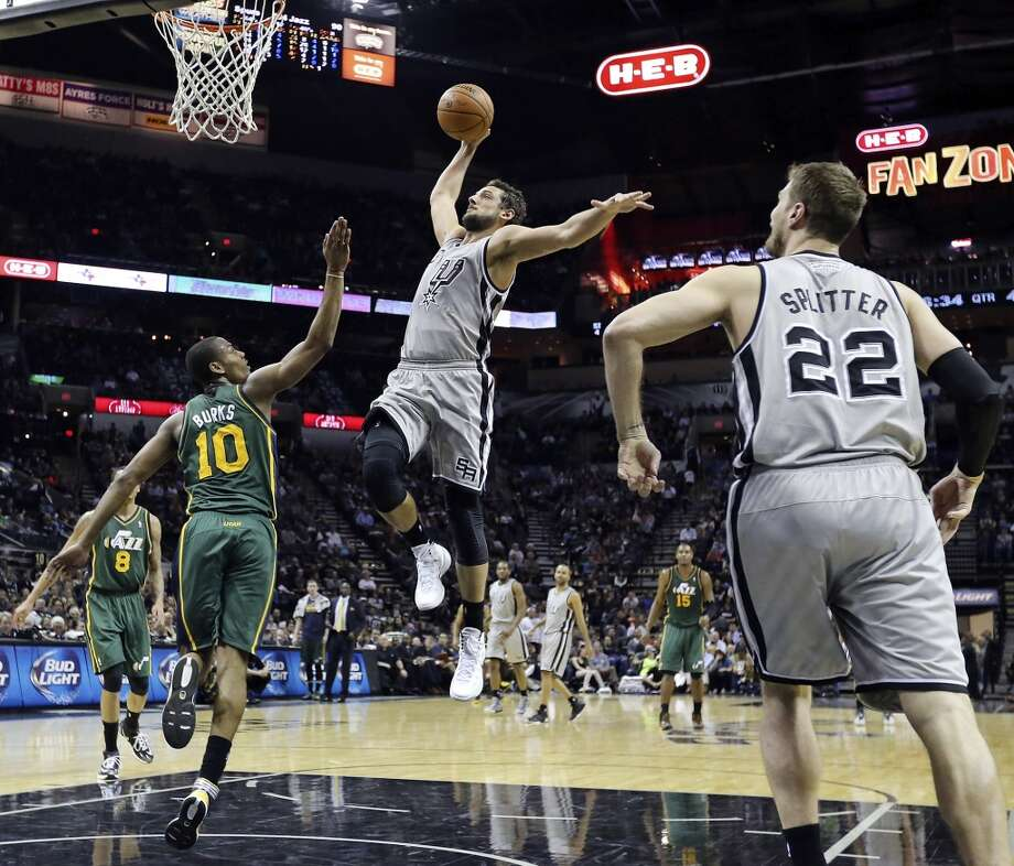 San Antonio Spurs' Marco Belinelli goes up for a dunk around Utah Jazz's Alec Burks as Tiago Splitter looks on during second half action Sunday March 16, 2014 at the AT&T Center. The Spurs won 122-104. Photo: San Antonio Express-News