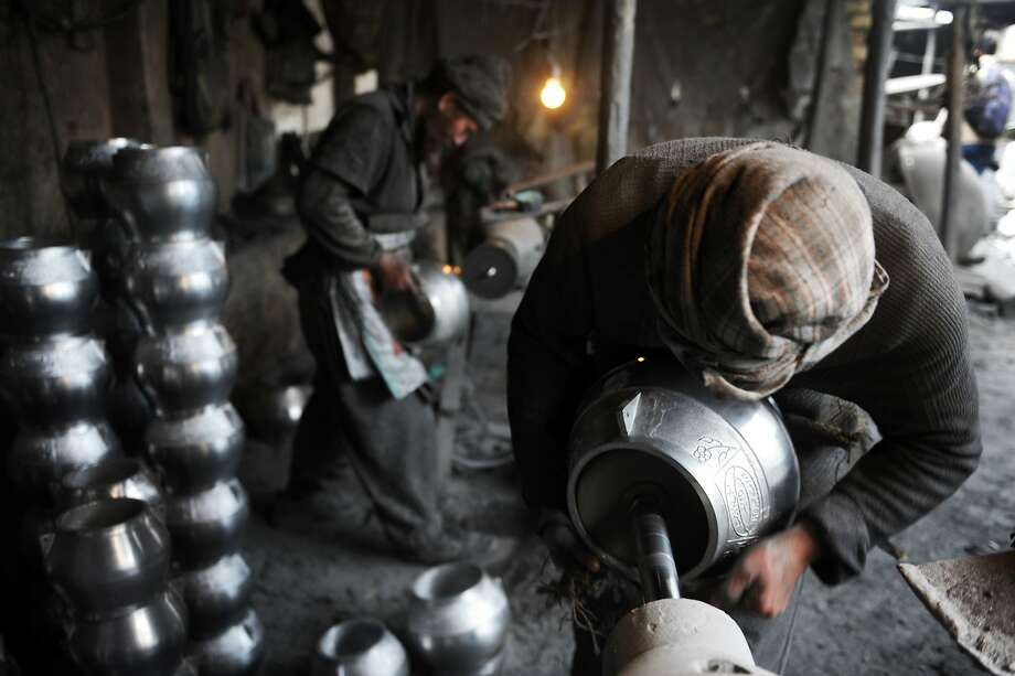 In this photograph taken on March 13, 2014, Afghan labourer Samad, 32, polishes a metal pot at a workshop in Mazar-i-Sharif. Samad works from dawn until dusk in a small factory where he earns around 1.5 USD per day. The factory produces around 50 pots daily, that are mainly used in cooking, by recycling metal scraps. AFP PHOTO/FARSHAD USYANFARSHAD USYAN/AFP/Getty Images Photo: Farshad Usyan, AFP/Getty Images