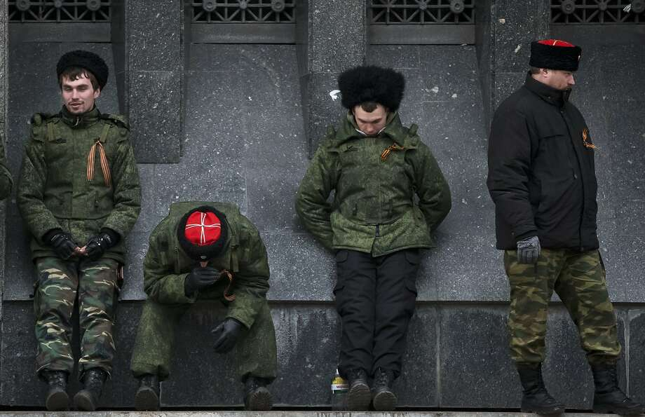 Cossacks guard the regional parliament building during the Crimean referendum in Simferopol, Ukraine, Sunday, March 16, 2014. Residents of Ukraine's Crimea region are voting in a contentious referendum on whether to split off and seek annexation by Russia. (AP Photo/Vadim Ghirda) Photo: Vadim Ghirda, Associated Press