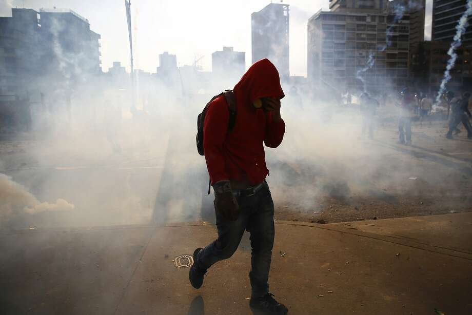 An anti-government protester walks amidst teargas during clashes with police at Altamira square in Caracas March 16, 2014. Opponents of Venezuela's socialist government marched on Sunday to protest against alleged Cuban interference in the armed forces, with clashes breaking out afterwards in a Caracas square. Several thousand people marched towards the Carlota military air base in the latest of daily demonstrations against President Nicolas Maduro's government that began in early February. REUTERS/Jorge Silva (VENEZUELA - Tags: POLITICS CIVIL UNREST) Photo: Jorge Silva, Reuters