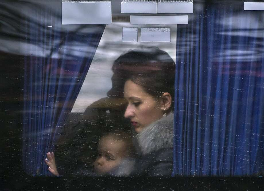 A woman holds a child as they ride on a bus in Simferopol, Ukraine, Sunday, March 16, 2014. Residents of Ukraine's Crimea region are voting in a contentious referendum on whether to split off and seek annexation by Russia. (AP Photo/Vadim Ghirda) Photo: Vadim Ghirda, Associated Press