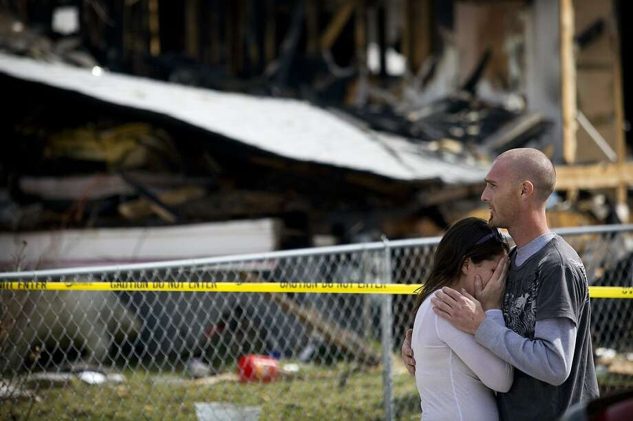 Jessica Bell, left, is embraced by her fiance Brian Page after arriving at the scene of a gas explosion and fire that destroyed the home of Bell's mother, Glenda Wyatt, in Provo, Utah, Sunday, March 16, 2014. Wyatt was pulled from the rubble by neighbors and was transported by ambulance to Utah Valley Regional Medical Center with burns to her face and arms. (AP Photo/Daily Herald, Mark Johnston) Photo: Mark Johnston, Associated Press