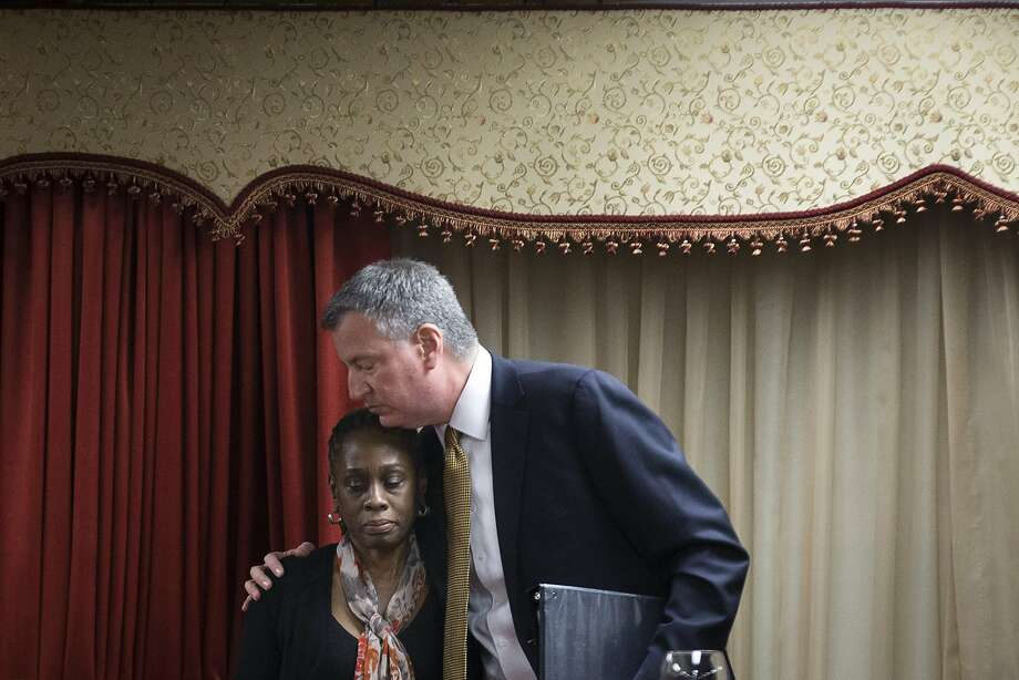 New York City Mayor Bill de Blasio, right, hugs his wife Chirlane McCray after speaking at the Church of God of Third Avenue as the congregation welcomed members of the Spanish Christian Church after the church was destroyed by Wednesday's explosion in the East Harlem neighborhood of New York, Sunday, March 16, 2014. The Spanish Christian Church was located on the first floor of one of the destroyed buildings. On Saturday a crew at the blast site found a Bible in the rubble and returned it to the church's pastor. (AP Photo/John Minchillo) Photo: John Minchillo, Associated Press