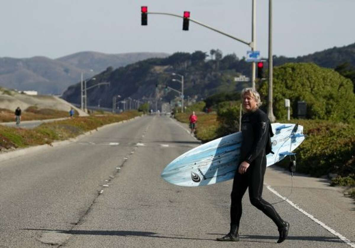 A surfer crosses the Great Highway in San Francisco's Outer Sunset neighborhood.