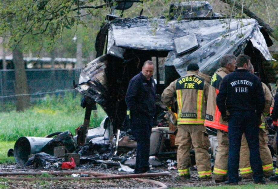 Firefighters investigate the scene of a fatal fire Monday morning at a mobile home in the 5400 block of Van Zandt.