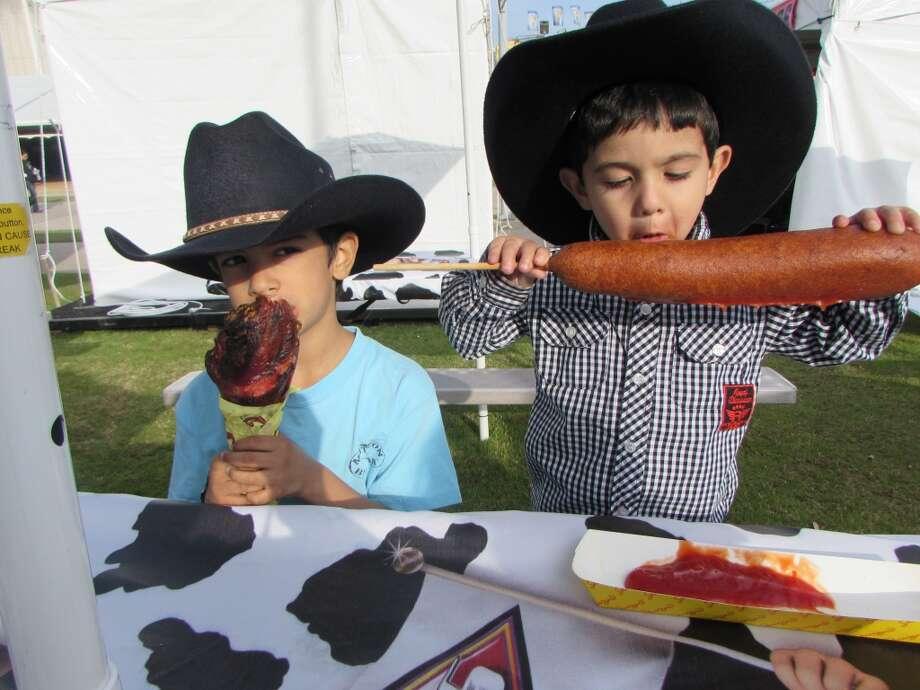 My boys enjoying a Turkey leg and a Texas sized Corndog at the Houston Livestock and Rodeo John Vargas