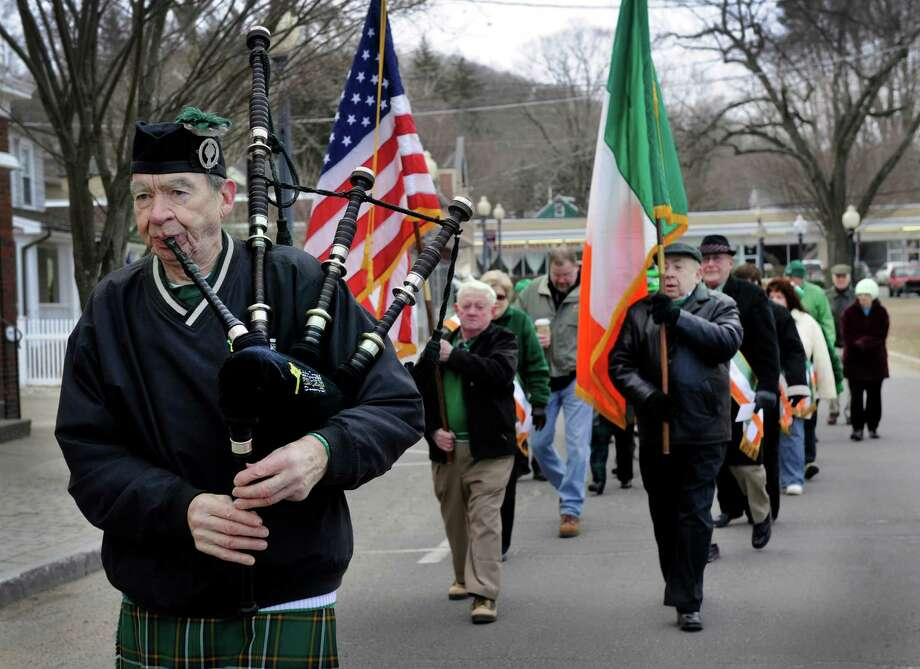 From left, Peter Hearty of New Fairfield, Conn., plays the bagpipes, Michael Keane of Danbury carries the American flag and Jim Palardy of Bethel, carries the Irish flag, in a short St. Patrick's Day parade from P.T.Barnum Square in Bethel to Town Hall for the second of two flag raisings followed by refreshments. The event, organized by the Ancient Order of Hibernians in Danbury, was one of several honoring St. Patrick in the area Monday. Photo: Carol Kaliff / The News-Times
