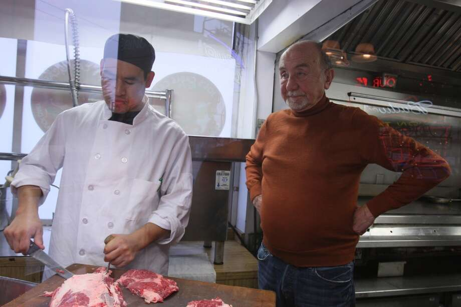 Ricardo Hernandez trims the fat from a piece of meat while restaurant owner Joe Obegi oversees the process at the Joe's Cable Car Restaurant in San Francisco, Calif. on Saturday, Feb. 8, 2014. Joe's hamburgers are made from beef chuck and ribeye. Photo: Andre Zandona, The Chronicle