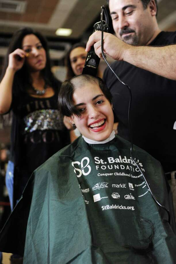 Senior Mariana Cordero has her head shaved for a fundraiser to benefit the St. Baldrick's Foundation at Greenwich High School by Eric Alfano owner of  Generations in Old Greenwich on Monday March 17, 2014. Photo: Dru Nadler / Stamford Advocate Freelance