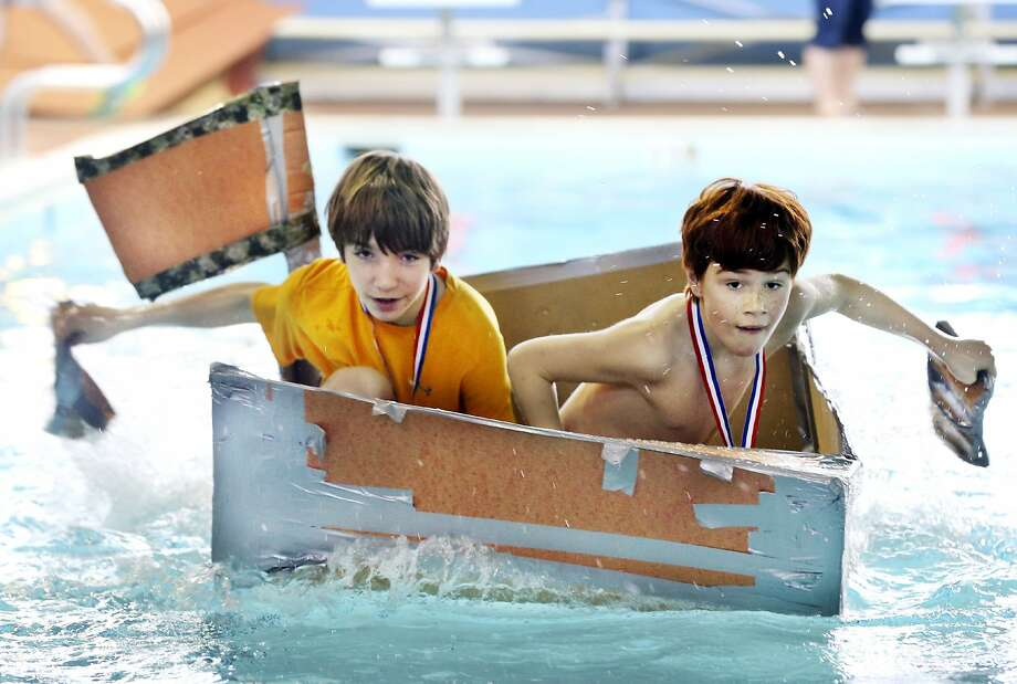 Rub a dub dub: Emmett Maiberger and Logan Chaile paddle their cardboard boat across 