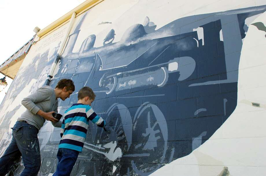 In loco parentis:Artist Justine Wollaston instructs Tyler Buck, who's helping her   paint a steam engine mural for Madam's on McCart in downtown Krum, Texas. Photo: David Minton, Associated Press