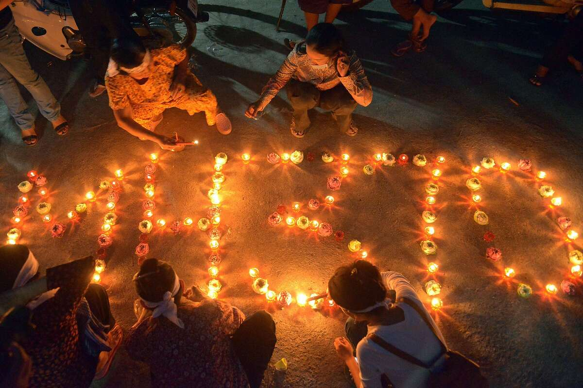 TOPSHOTS Cambodian residents of a community light candles as they pray for the missing Malaysia Airlines flight MH370 at their village in Phnom Penh on March 17, 2014. An investigation into the pilots of missing Malaysia Airlines flight 370 intensified on March 17 after officials confirmed that the last words spoken from the cockpit came after a key signalling system was manually disabled. AFP PHOTO/ TANG CHHIN SOTHYTANG CHHIN SOTHY/AFP/Getty Images