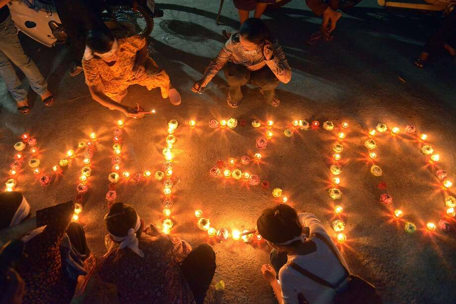 Prayer vigil for the travelers: Villagers near Phnom Penh light candles as they pray for the passengers of missing 