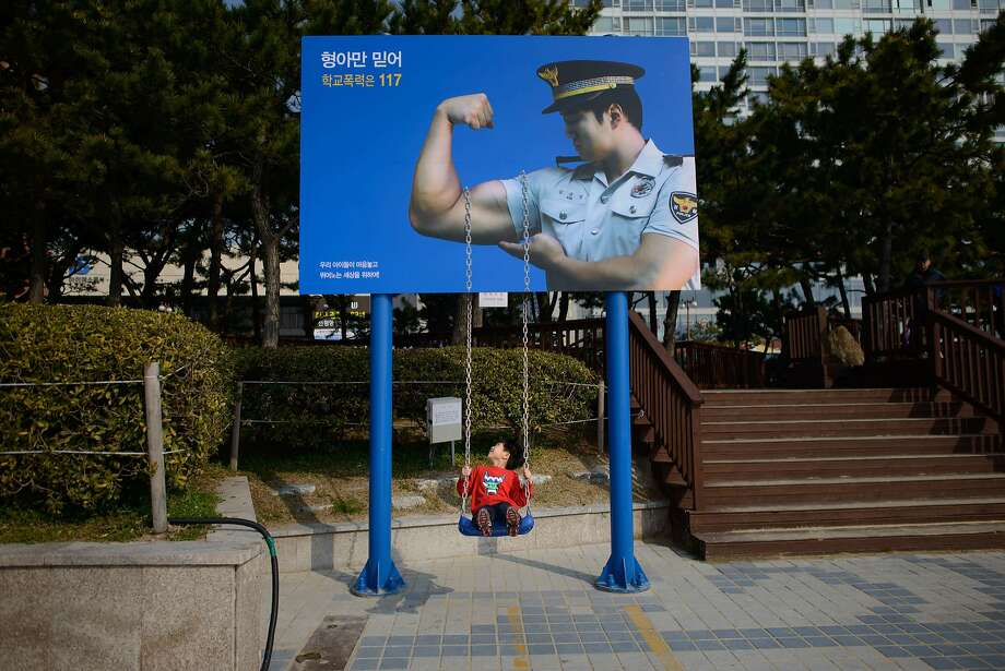 Nice guns, officer:In Busan, South Korea, a child swings on the strength of   policeman's biceps. Photo: Ed Jones, AFP/Getty Images