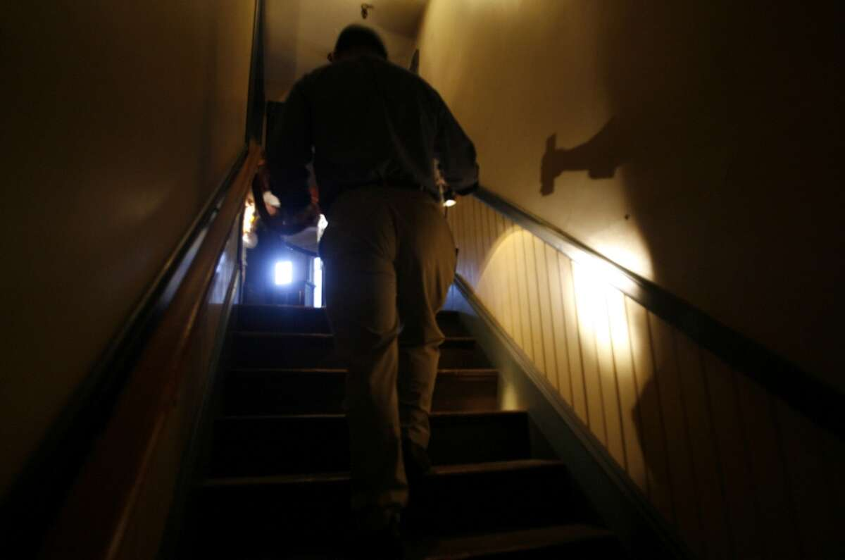 An employee of the mansion makes his way up a back staircase.