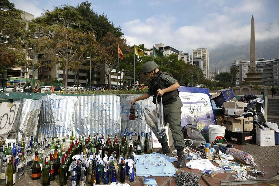 A National Guard member removes a Molotov cocktail at Altamira Square in Caracas. Photo: Carlos Garcia Rawlins, Reuters