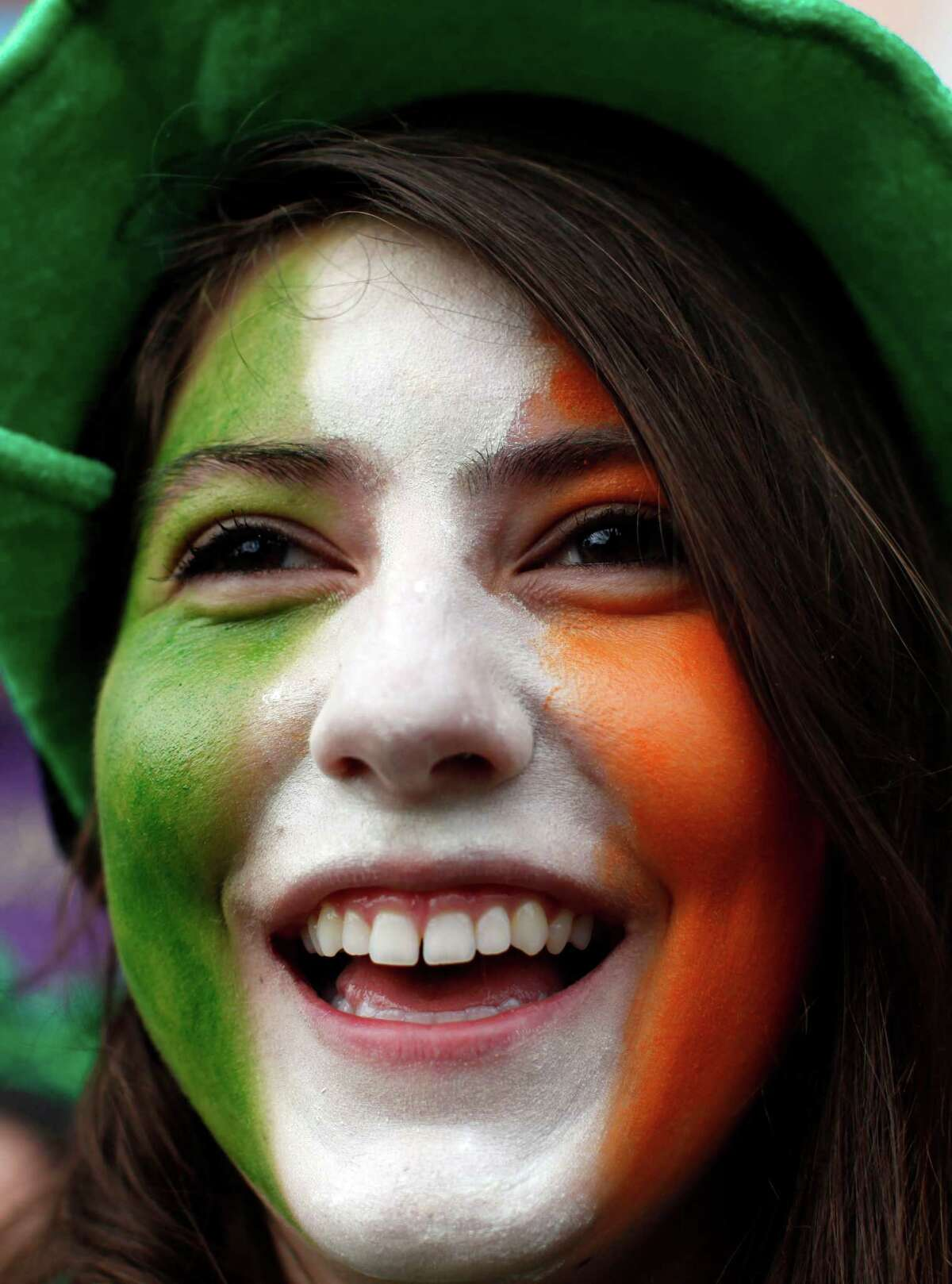 A spectator with the flag of Ireland painted on her face watches the parade during St Patrick's Day festivities in Dublin.