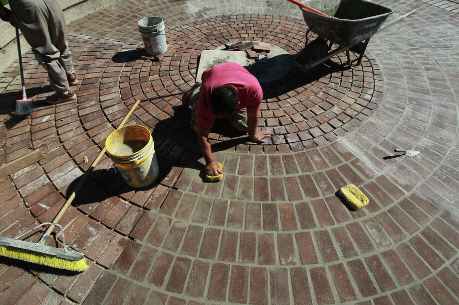 Luis Martinez (center) and Antonio Hurtado (left) work with new pavers at Travis Park Monday March 17, 2014. The park is going through a $500,000 renovation and wil have a number of upgrades including a mini dog park and a mobile kiosk with games. Photo: John Davenport, San Antonio Express-News / ©San Antonio Express-News/Photo may be sold to the public