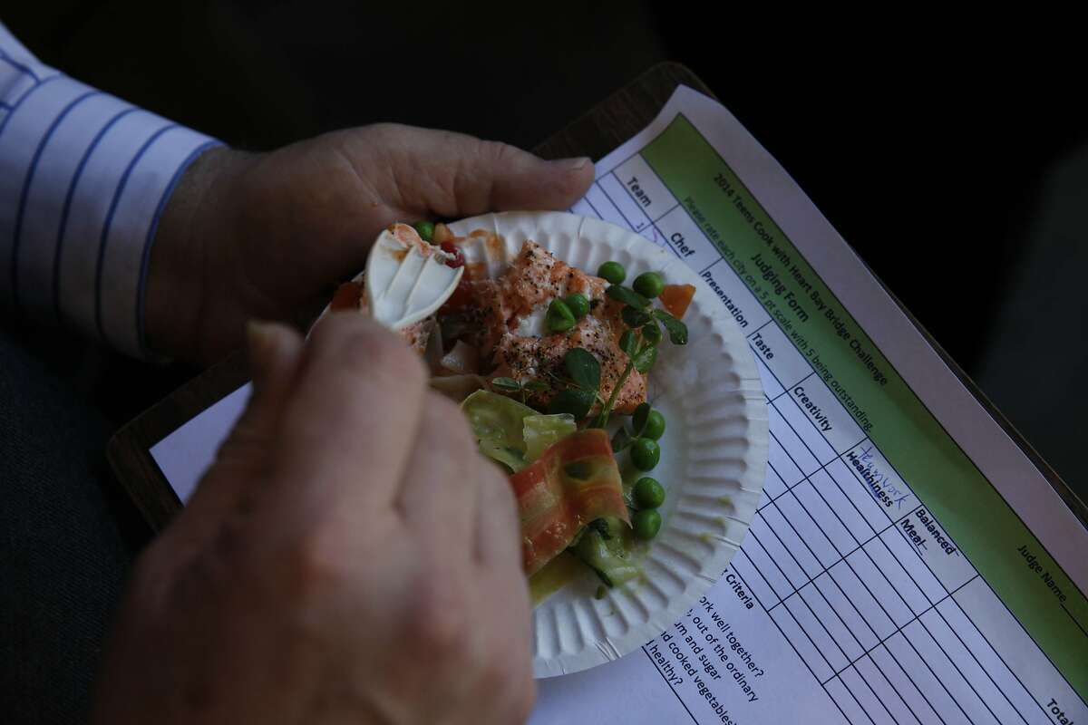 Judge Bob Klein, owner of Oliveto restaurant in Oakland, samples a salmon dish at the Teens Cook With Heart Bay Bridge Challenge.